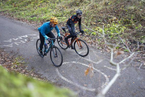 o nas, Trójmiejski Park Krajobrazowy, kolarze jadący pod górę w lesie, foto Anna Tkocz
